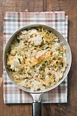 Pan-cooked rice and fish dish with lemon zest from above