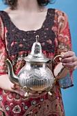 Frau hält orientalische Teekanne