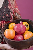 Woman holding fresh fruit in wooden bowl