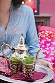 Woman serving peppermint tea on tray