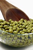 Peas in glass bowl with wooden spoon