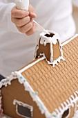 Kind verziert Lebkuchenhaus mit Spritztüte