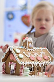Small girl decorating gingerbread house