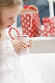 Small girl holding cup of cocoa with candy cane