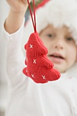 Child in Father Christmas hat holding Xmas tree ornament