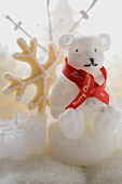 Polar bear candle with ribbon, snowflake biscuit behind