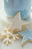 Three iced Christmas biscuits in front of blue cup