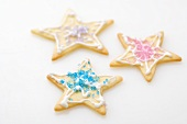 Three star biscuits decorated with coloured sugar