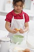 Small girl breaking an egg