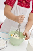 Small girl mixing egg, flour and butter with whisk