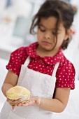 Small girl forming dough into a ball