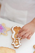 Child decorating Christmas biscuit with silver balls