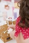 Kleines Mädchen verziert Lebkuchenhaus mit Spritztüte