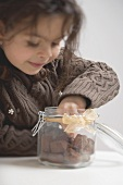 Girl reaching for chocolate biscuits in storage jar