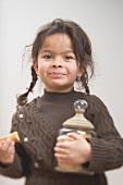 Small girl holding storage jar full of shortbread