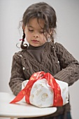 Small girl with cake in Christmas wrapping paper