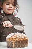 Small girl sprinkling icing sugar on almond cake