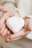 Child holding Christmas tree ornament