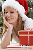 Woman in Father Christmas hat looking at Christmas parcel