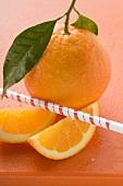 Orange with stalk and leaf, orange wedges, straw