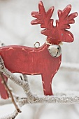 Wooden reindeer on frost-covered branch out of doors