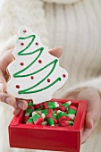 Woman holding Christmas tree biscuit and sweets