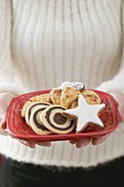 Woman holding plate of Christmas biscuits