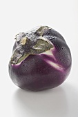 A round aubergine with drops of water