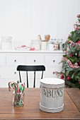 Candy canes & cookie tin in kitchen with Christmas decorations