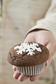 Hand holding chocolate muffin (Christmas)