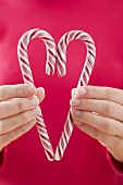 Woman holding two candy canes together to form a heart
