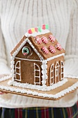 Woman holding gingerbread house
