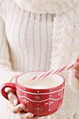 Woman holding cup of cocoa and candy cane (Christmas)