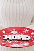 Hands holding festive plate with the word HOHO