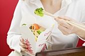 Frau isst asiatisches Gemüsegericht im Take-Out-Behälter
