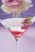 Martini with strawberry in glass, rose in background