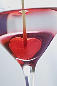 Martini with jelly heart in glass (close-up)