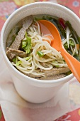 Asian noodle soup with beef in polystyrene cup