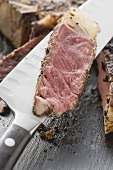 Slice of spicy rib eye steak on knife (close-up)