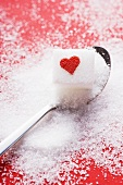 Sugar cube with red heart on spoon
