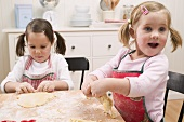 Two small girls kneading dough