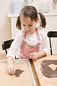 Small girl placing chocolate biscuit on baking tray