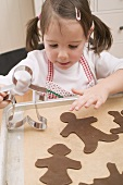 Small girl placing chocolate biscuits on baking tray