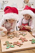 Two small girls decorating gingerbread men