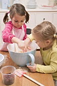 Two small girls tasting mixture from a mixing bowl