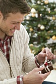 Mann öffnet Weihnachtspäckchen