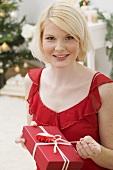 Frau öffnet Weihnachtspäckchen
