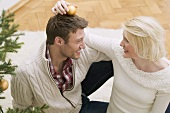 Woman putting Christmas bauble on man's head