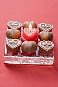 Heart-shaped candle surrounded by chocolates