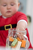 Baby taking sweets out of storage jar